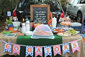 tailgate spread with assorted food and a go gators sign hanging on the front