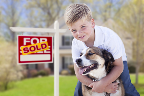 young boy hugging his dog in front of a for sale sign with sold over top it