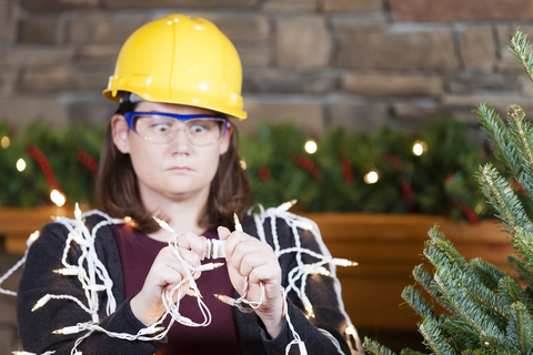 lady in a hardhat plugging in lights next to a christmas tree