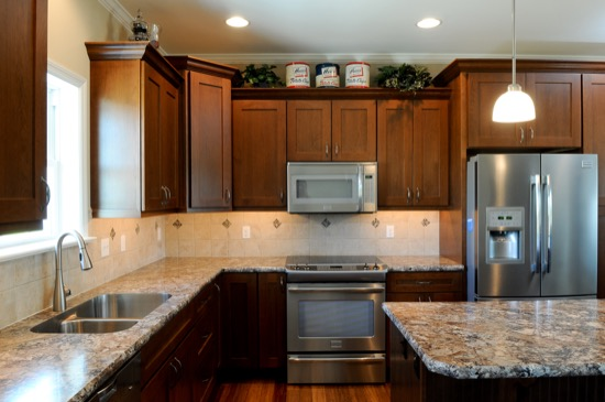kitchen with brown cabinets granite countertops, and stainless steel appliances
