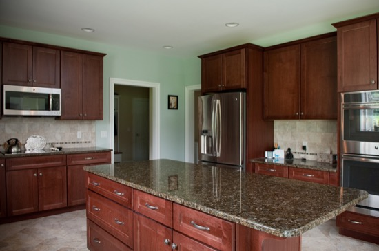 kitchen with brown cabinets, granite countertops, kitchen island, and stainless steel appliances