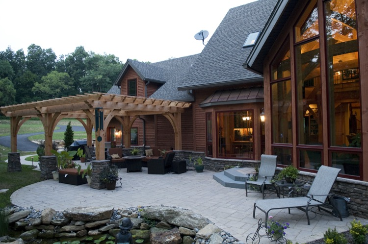 landscaped patio and pergola at back of home