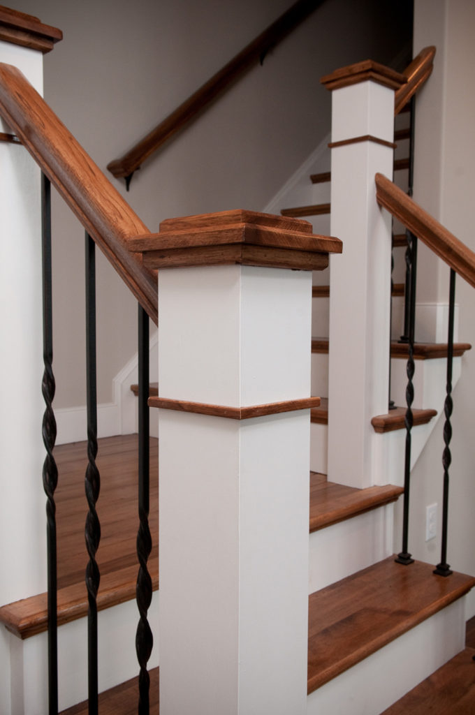 Custom Newel Post with Iron Pickets on a staircase