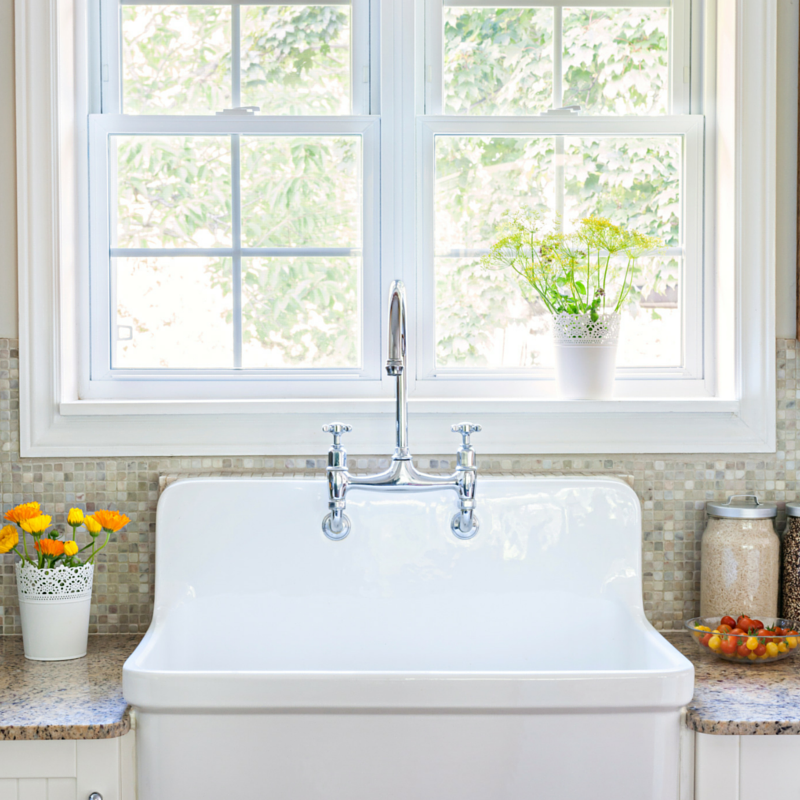 farmhouse sink underneath large white window