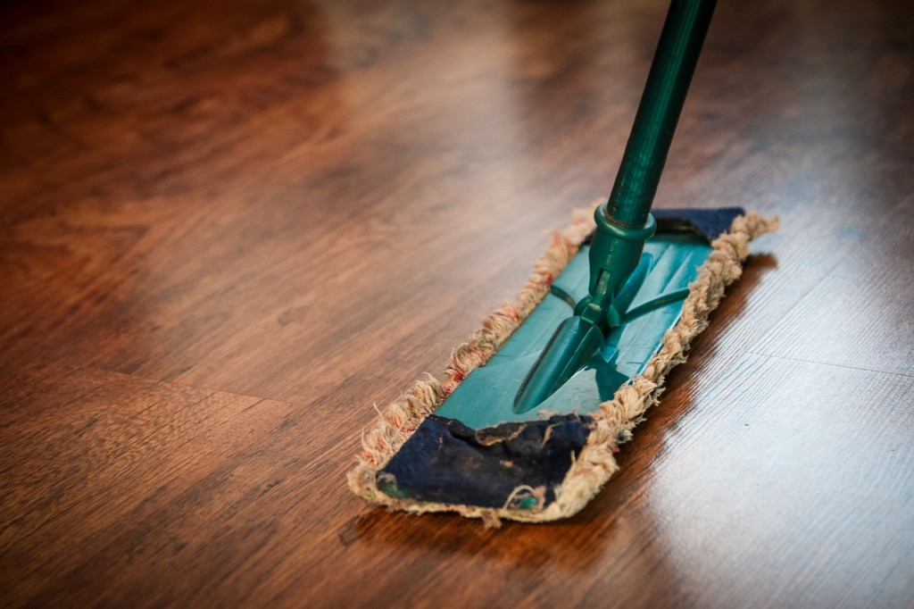 old mop duster cleaning a hardwood floor