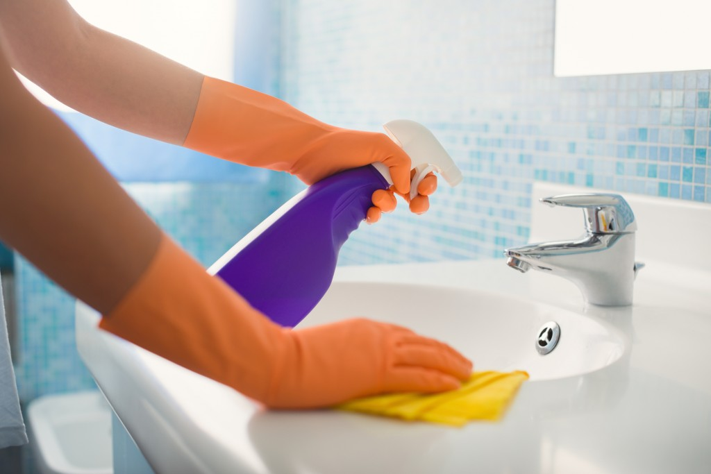 cleaning a bathroom sink with a purple spray-bottle and yellow cloth