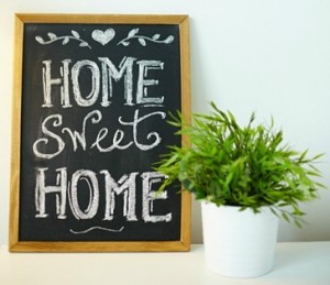 home sweet home on small chalkboard next to potted plant