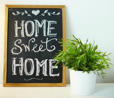 home sweet home written on blackboard next to a small potted houseplant