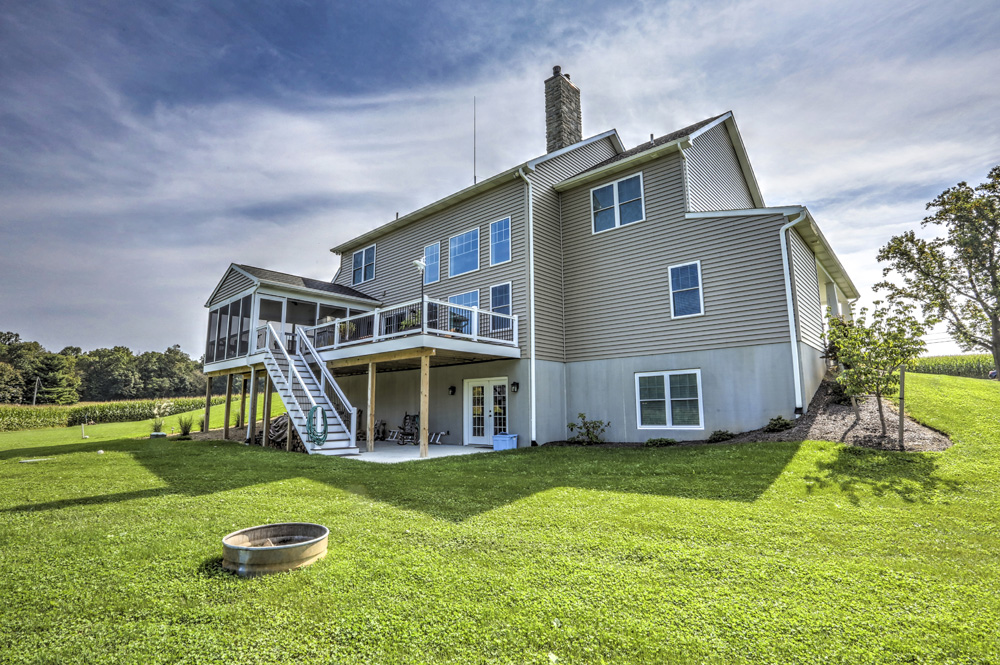 back of home with deck, sunroom, large yard and fire pit