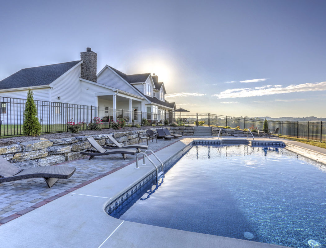 fenced in in-ground pool area with lounge chairs
