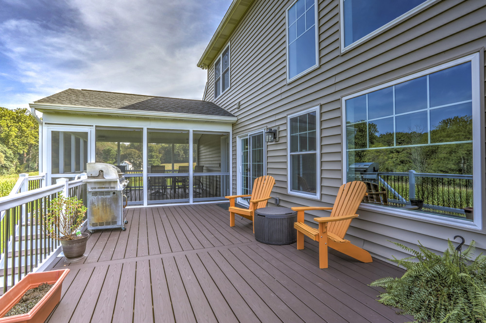 deck with outdoor furniture and grill. behind it is a screened in area
