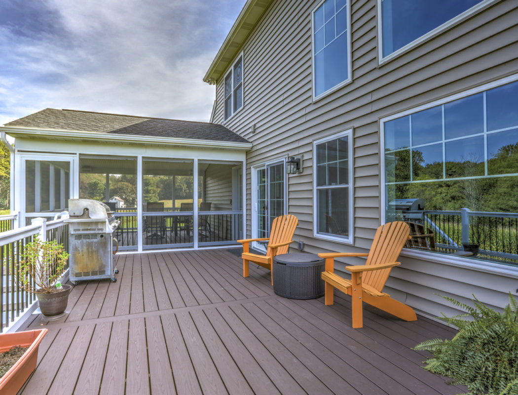 a deck with 2 orange chairs and grill