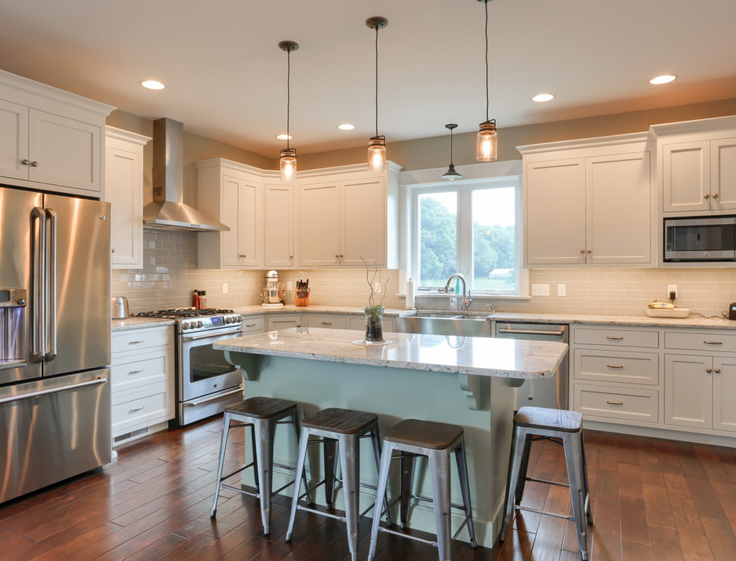 large, open kitchen with island and white cabinets