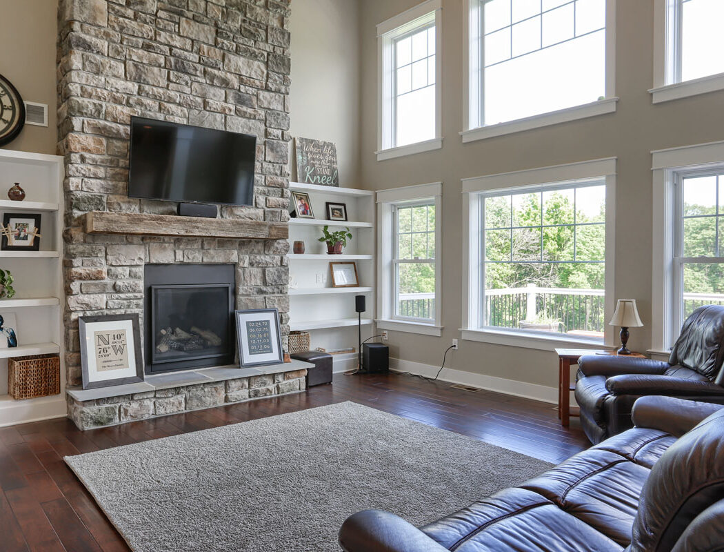 living room area with stone fireplace and a mounted TV