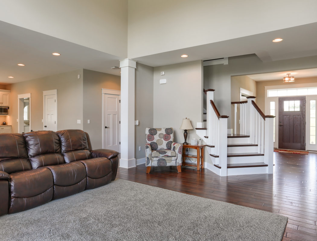 Living room area with leather couch. Staircase heading to second floor is just past the entryway on the right