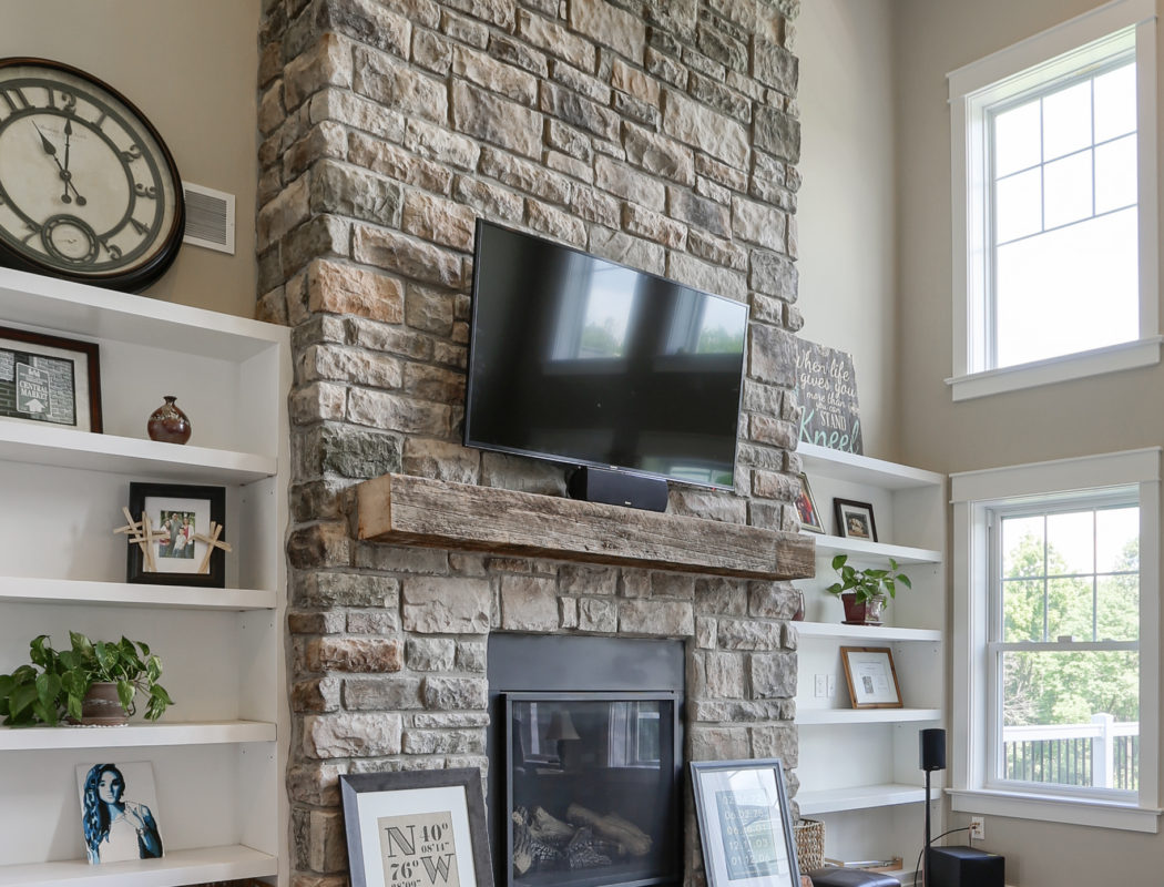 stone fireplace with mounted TV overhead