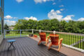 two orange chairs on a deck overlooking a lawn