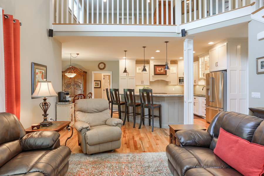 looking into the kitchen past leather furniture and the island bar with 3 wood chairs