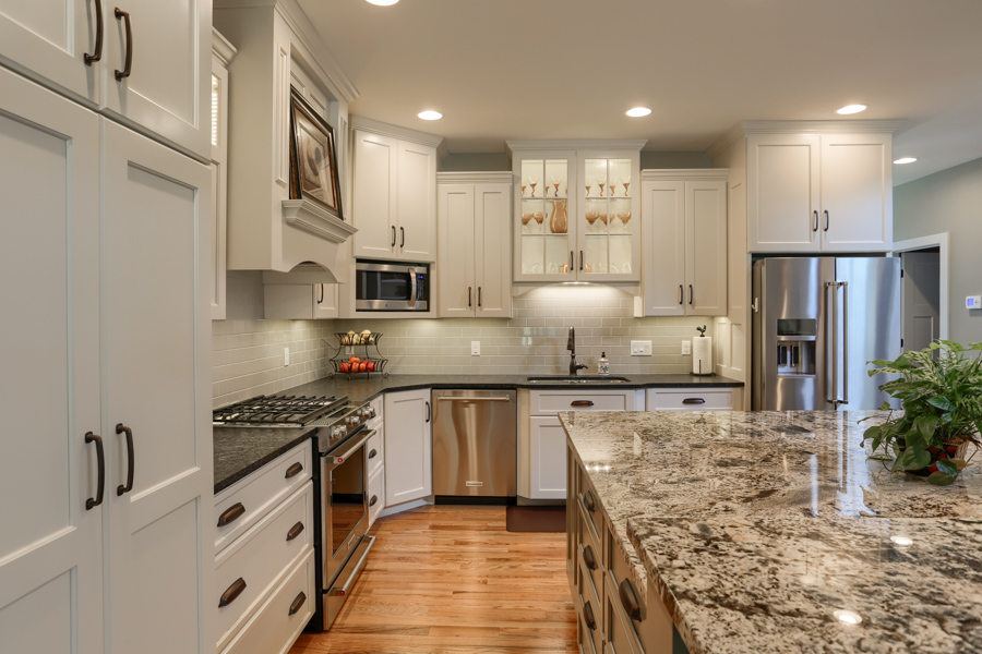 kitchen with white cabinets, large stone countertops and stainless steel appliances