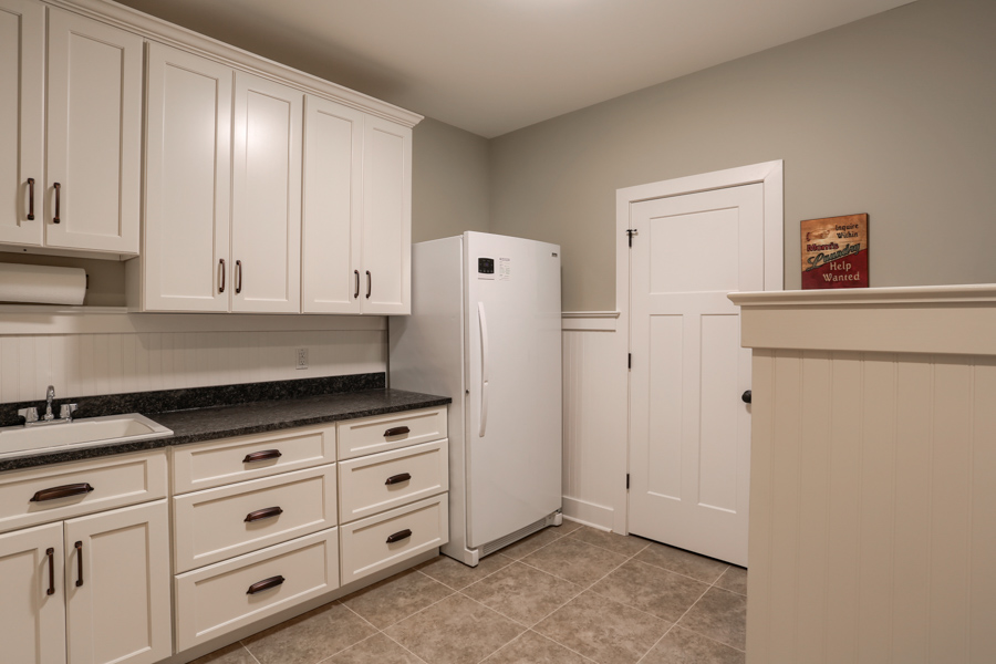 fridge and sink area with white cabinets