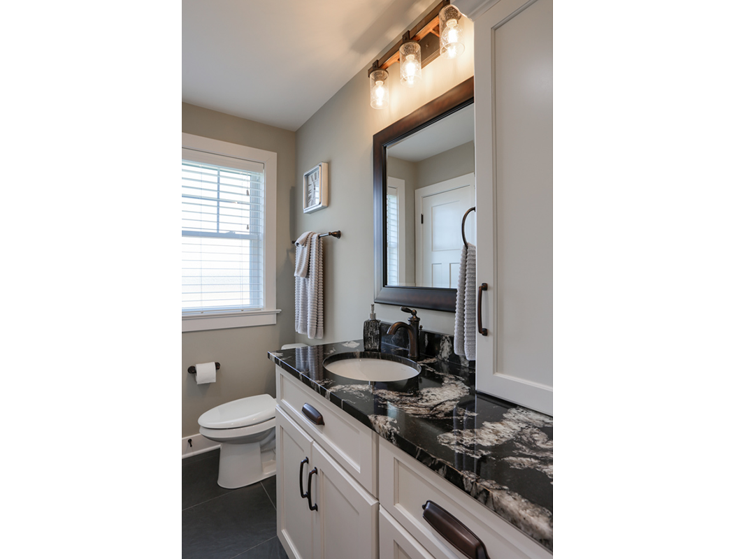 toilet and sink with stone countertop