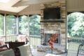 stone fireplace with a tv mounted above it