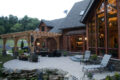 back of a log home with a wood shade structure and hardscaped patio