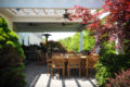 outdoor living area with various plants, patio furniture, fans and a grill