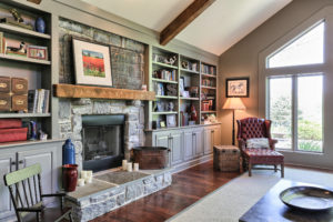 family room with stone fireplace and built in shelves