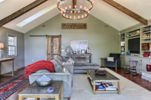 after vaulted ceiling family room with built in shelves and sliding barn door