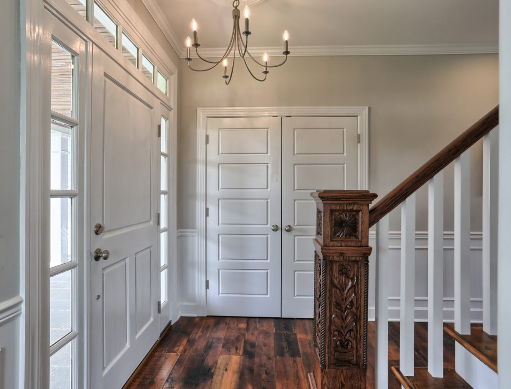 custom home entryway and wood railing for staircase