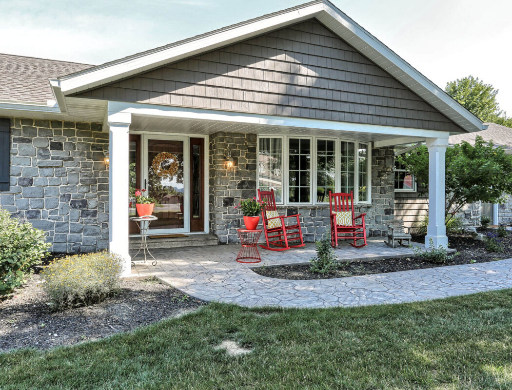 a stone walkway leading up to a nice porch with 2 red rocking chairs
