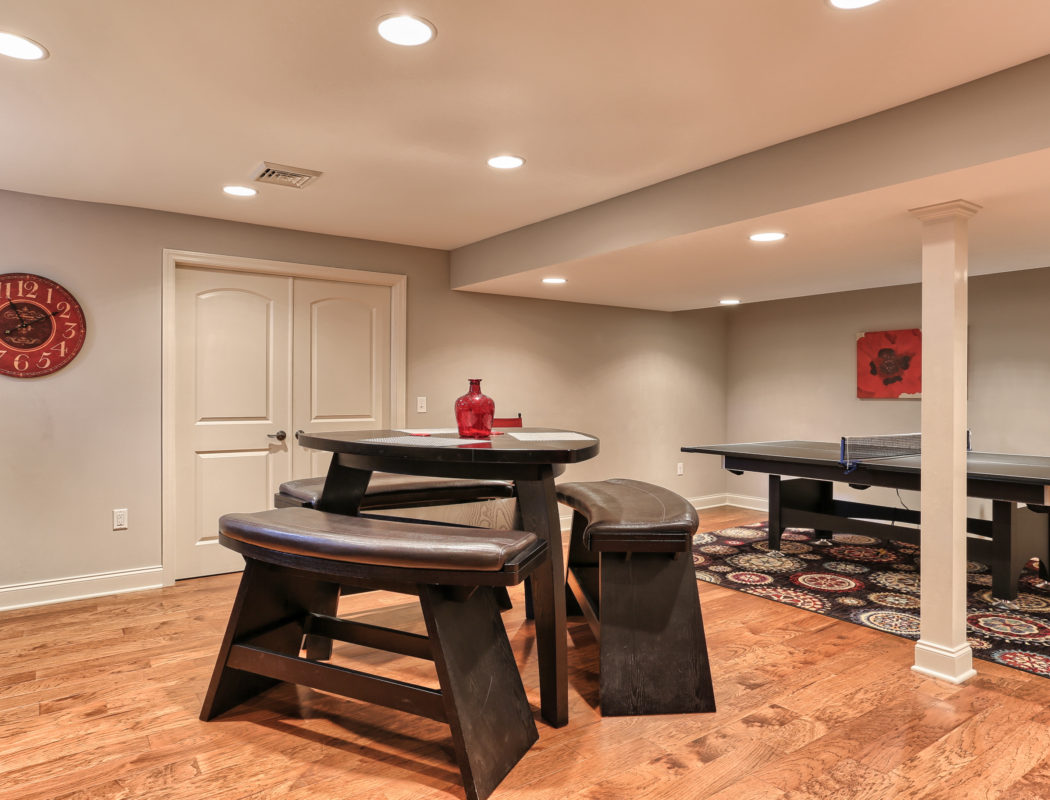 seating area with a pingpong table in the back of a recent Metzler Home Builders basement renovation