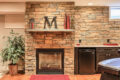 stone wall, fireplace, and refrigerator in a finished basement