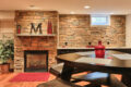 stone wall, fireplace, and seating area in a finished basement