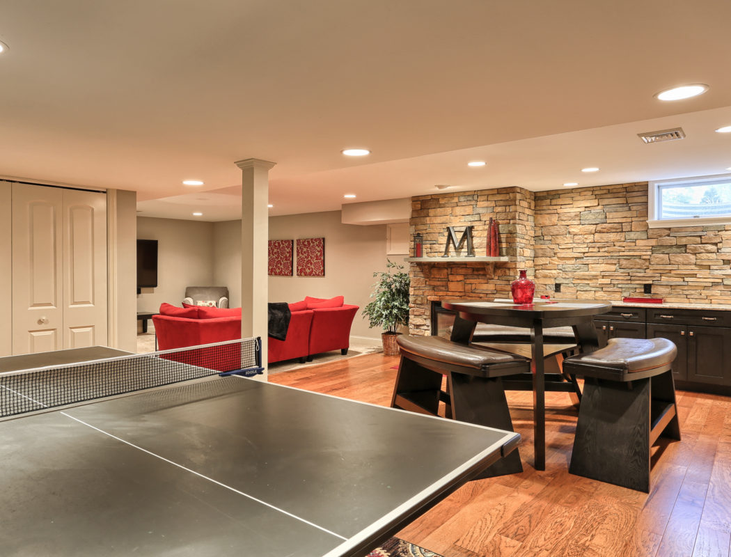 pingpong table, seating area, and a red couch inside a finished basement