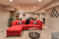 a red couch, seating area, and pingpong table in a renovated basement