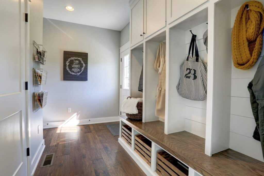sample mudroom build by Metzler Home Builders. shows shelving for coats, bags and jackets and storage shelves underneath